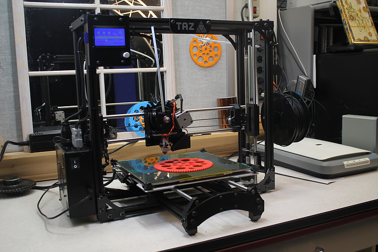 A 3D Printer printing a red gear.