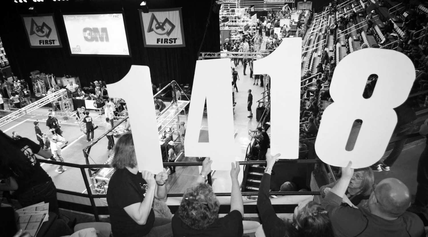 A black and white picture of team members holding up the numbers 1418.