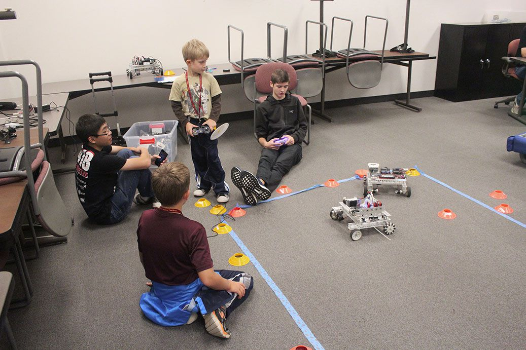 Children and a team member driving robots.