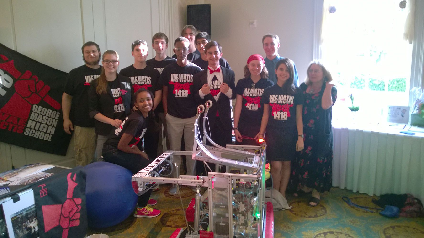 The team posing behind the robot.