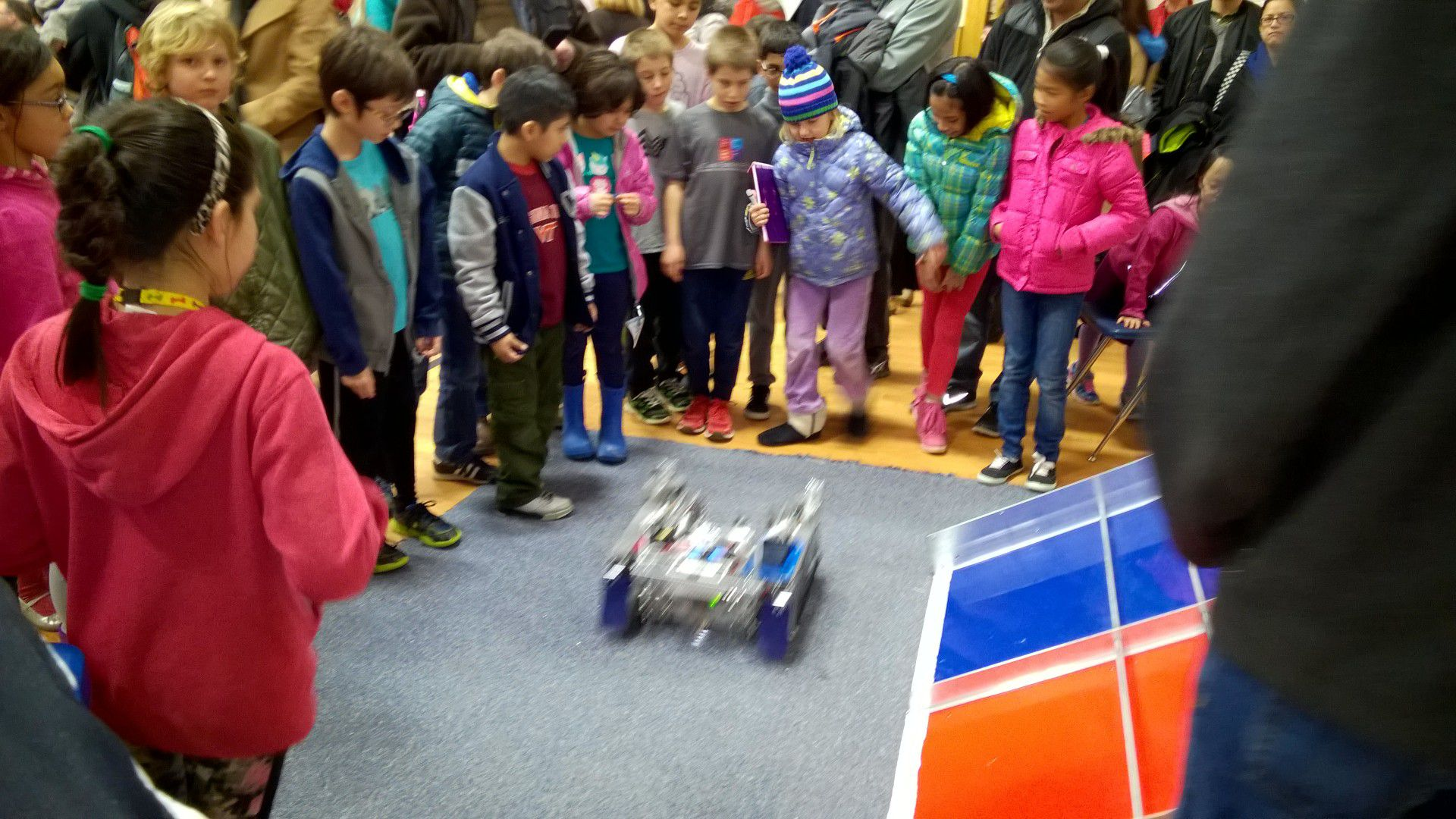 A crowd of children huddle around a robot in the center.