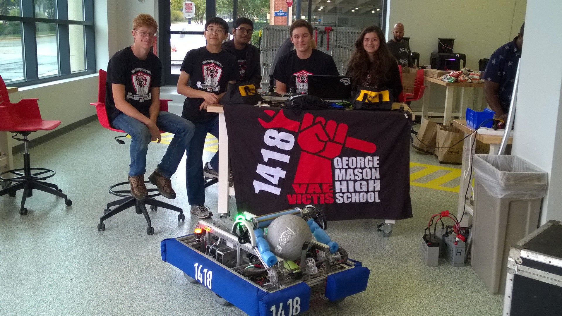 The team posing behind a 1418 banner with the robot in front.