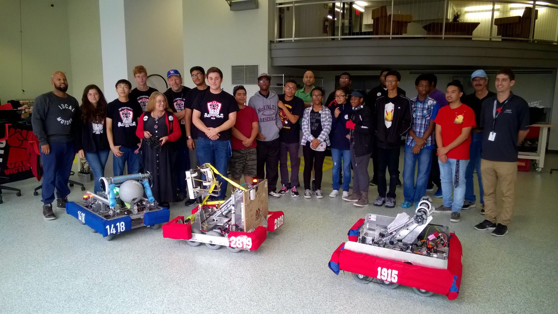 FRC Teams 1418, 1915, and 2819 posing behind their robots.