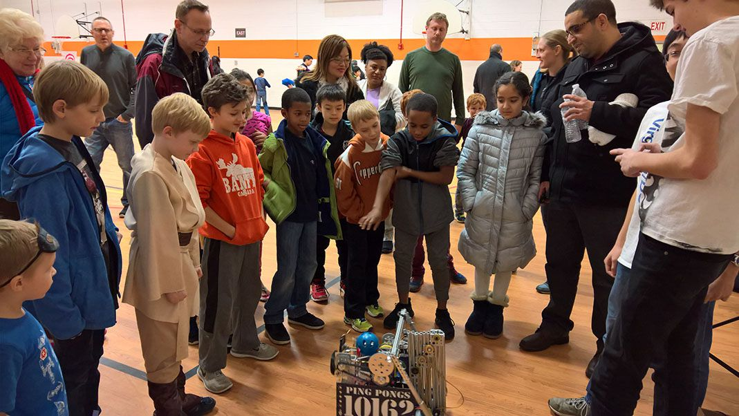 Children and parents huddled around a small robot.