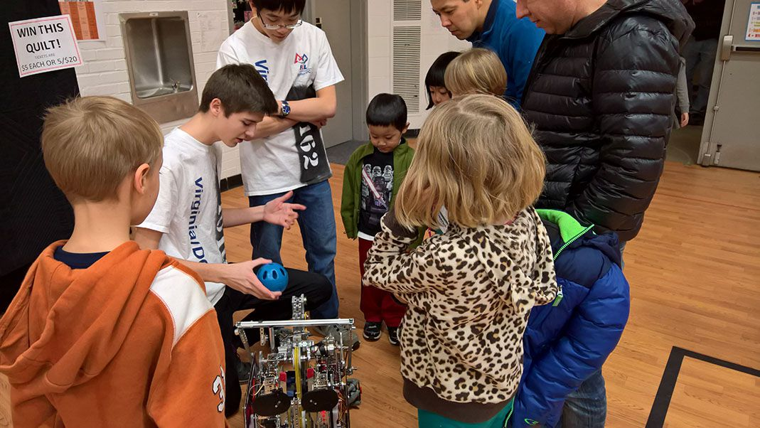 The team showing off a robot to children.