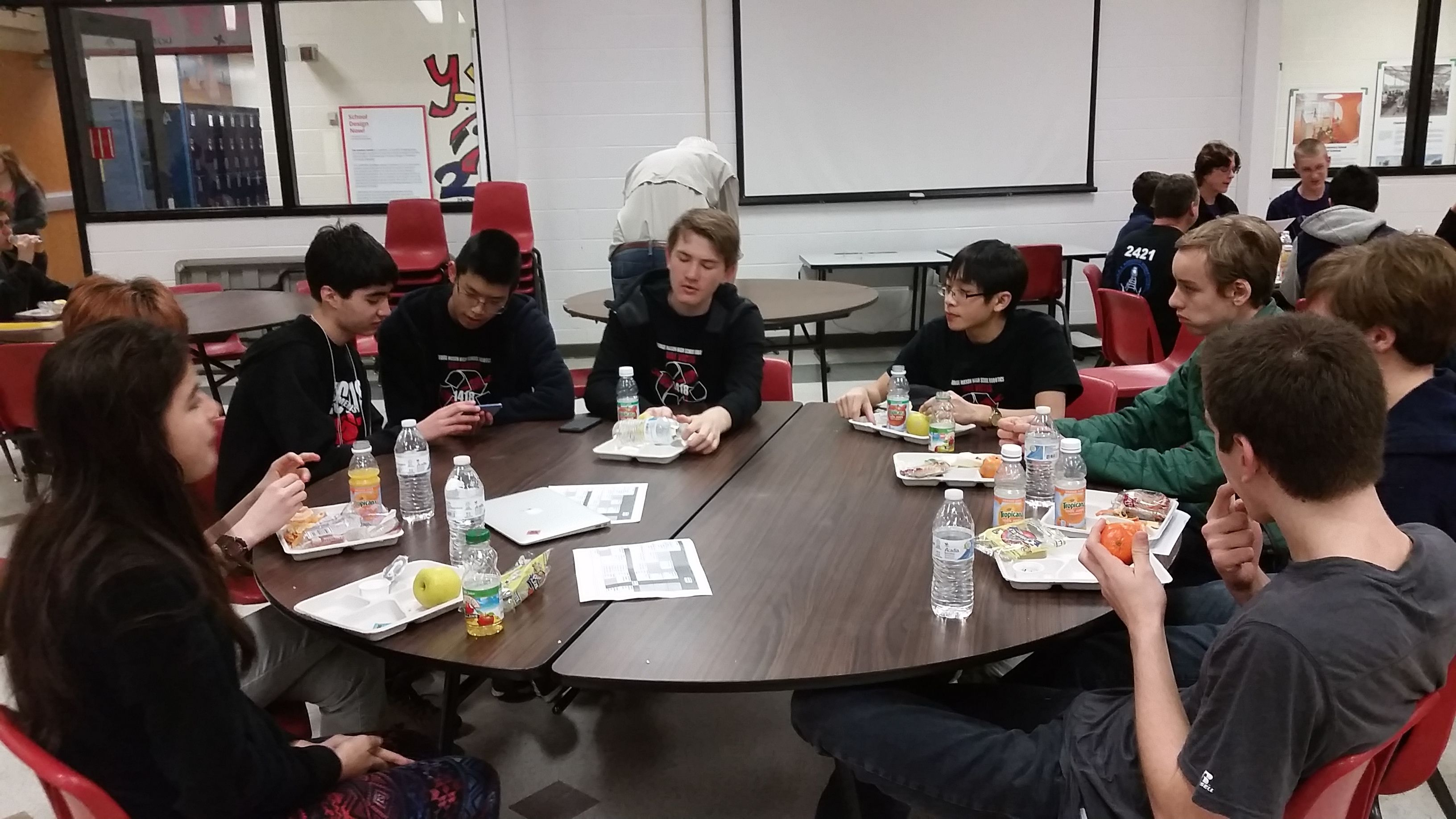 Students attending a 2015 workshop at a brown table.